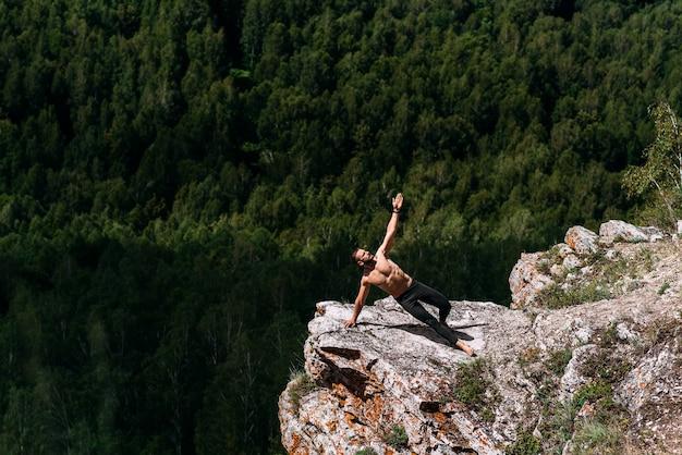 Un uomo sportivo fa yoga. uno stile di vita sano. la concentrazione del corpo. un uomo fa yoga in montagna. un uomo fa yoga su una roccia. un uomo medita nella natura. meditazione in montagna