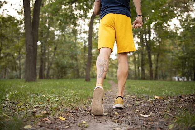 Uomo sportivo che va a fare jogging nella foresta da solo