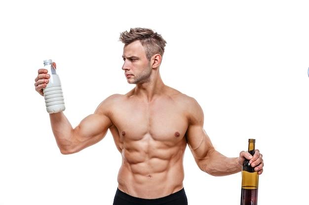 Uomo sportivo che tiene un vino e latte e affronta una scelta, uno stile di vita sano o alcol. salute, sport, scelta, cibo sano e concetto di stile di vita sano.
