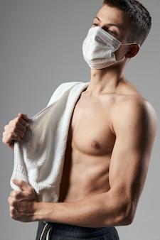 L'uomo sportivo in asciugamano maschera medica sulle spalle ha pompato il corpo