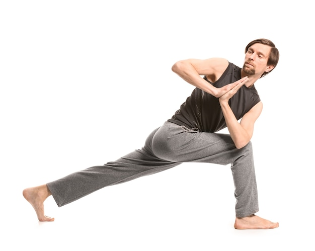 Uomo sportivo che pratica yoga su bianco