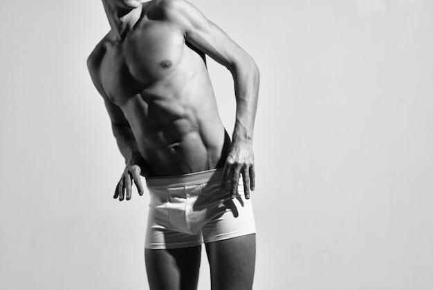 L'uomo sportivo ha pompato la posa dello stile di vita fitness in abs