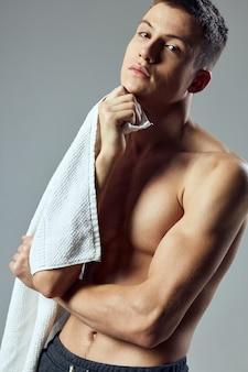 Uomo sportivo pompato corpo con un asciugamano in vista ritagliata primo piano mani.