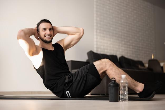 Pressa di pompaggio dell'uomo sportivo che si trova sulla stuoia. montare l'uomo felice facendo esercizi di fitness sul pavimento a casa. abbigliamento sportivo nero. uomo muscoloso che fa il suo esercizio mattutino preferito.