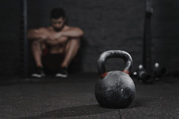 Uomo sportivo seduto in palestra che soffre di ripartizione da superare. concetto di sport di demotivazione. stress e stanchezza nello sport. allenamento con kettlebell crossfit.
