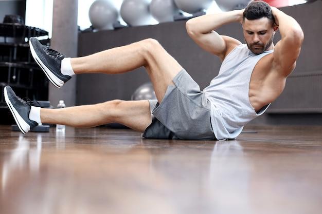 Uomo sportivo che si allunga e si riscalda facendo esercizi speciali per i muscoli prima di allenare il suo corpo.