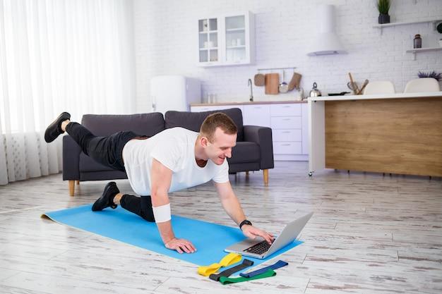 Un uomo sportivo in maglietta fa sport a casa nel suo appartamento spazioso e luminoso con interni minimalisti. sport su internet