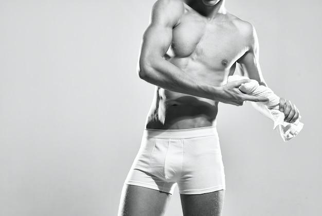 L'uomo sportivo in mutandine bianche ha pompato l'asciugamano per il corpo fitness