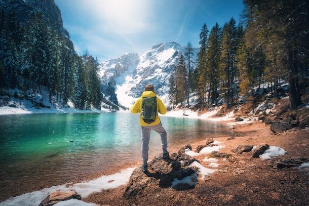 L'uomo sportivo con lo zaino sta stando sul lago vicino di pietra con acqua azzurrata al giorno soleggiato in autunno.
