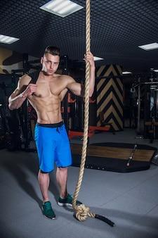 Uomo sportivo con grandi muscoli e schiena ampia si allena in palestra, fitness e pressa addominale pompata. uomo sexy in palestra con manubri