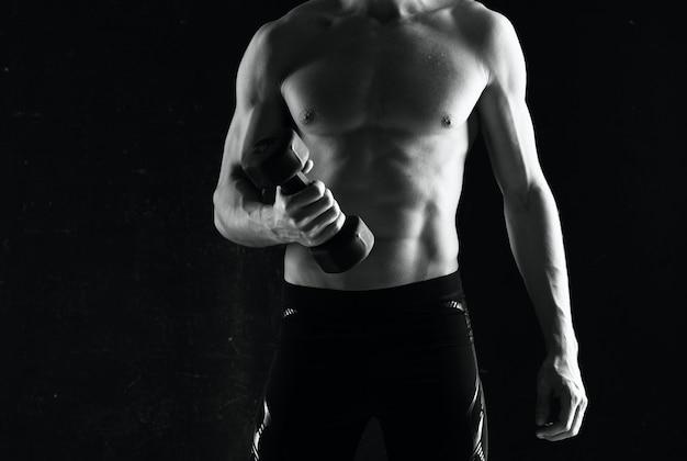 Uomo sportivo con manubri in mano che pompano i muscoli esercita sfondo scuro
