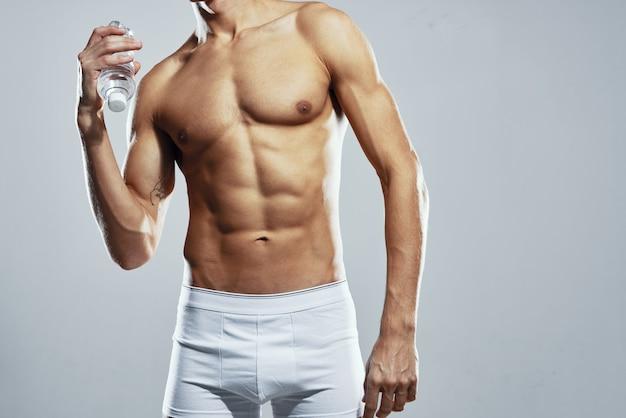 Uomo sportivo con corpo muscoloso pompato in pantaloncini bianchi allenamento sfondo chiaro