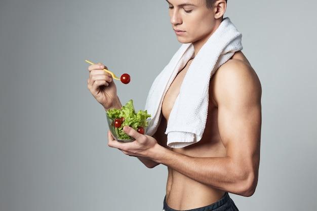 Uomo sportivo con asciugamano sulle spalle sul vegetarianismo cibo sano isolato.