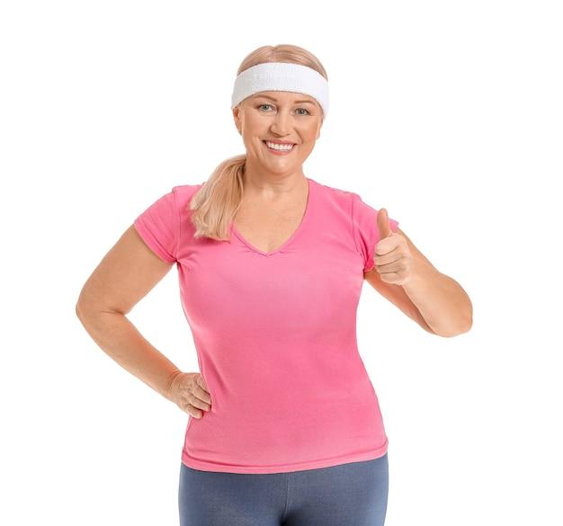 Donna matura sportiva che mostra pollice in su su bianco