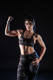 Donna muscolare sportiva su oscurità