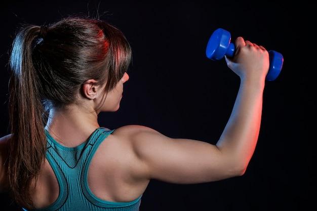 Donna muscolare sportiva con manubri su oscurità