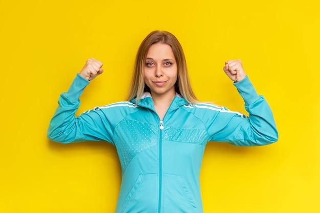 Atleta sportiva piuttosto caucasica giovane donna bionda in una giacca sportiva turchese mostra bicipiti isolati su una parete gialla di colore brillante
