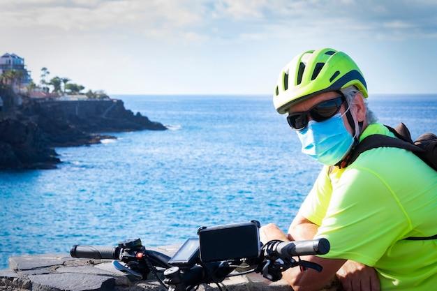 Uomo anziano sportivo con casco da bici e maschera medica per evitare l'infezione da coronavirus. usa una bici elettrica. orizzonte sull'acqua e sulla costa