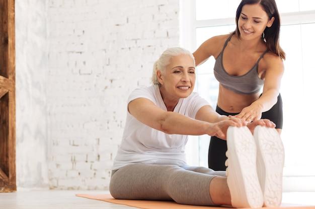 Sportiva da donna senior mantenendo il sorriso sul viso e seduta vicino al suo istruttore mentre mette le dita sulle scarpe da ginnastica