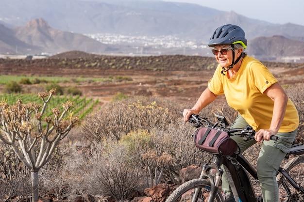 Donna anziana sportiva in escursione all'aperto sulla sua bici elettrica vigna verde e montagna sullo sfondo