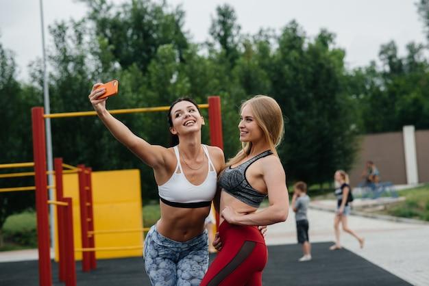 Ragazze sportive e sexy fanno selfie all'aperto. fitness, stile di vita sano