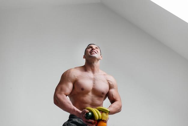 Ragazzo sexy sportivo in posa su uno spazio bianco con frutti luminosi. dieta. dieta sana.