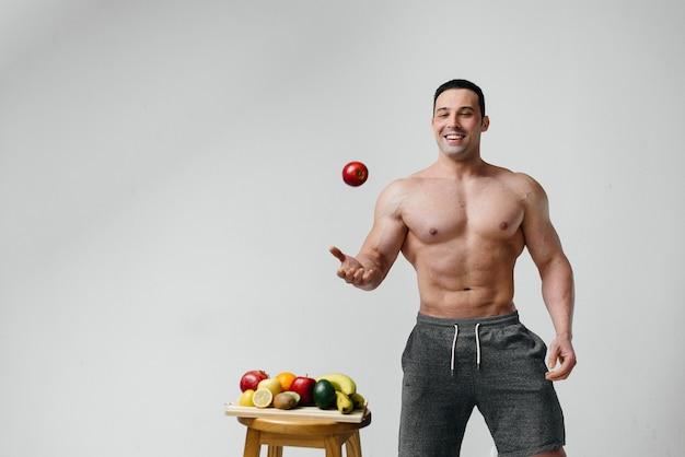 Ragazzo sexy sportivo in posa su un muro bianco con frutti luminosi. dieta. dieta sana.