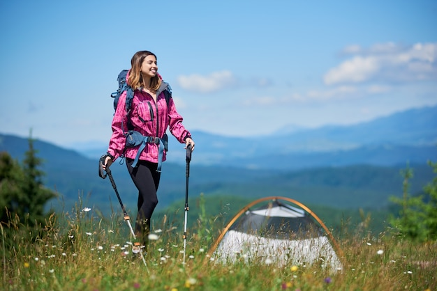 Viaggiatore femminile sorridente sportivo con zaino e bastoncini da trekking vicino alla tenda, in piedi sulla cima di una collina contro il cielo blu e nuvole, godendo la giornata di sole in montagna