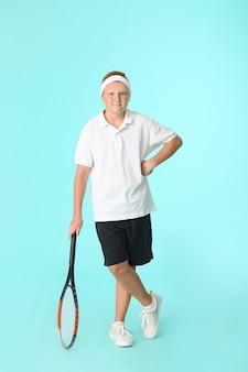 Ragazzo adolescente sportivo con racchetta da tennis sul colore