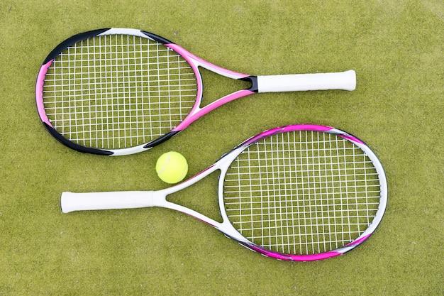 Racchette da tennis sportive con palla su sfondo verde