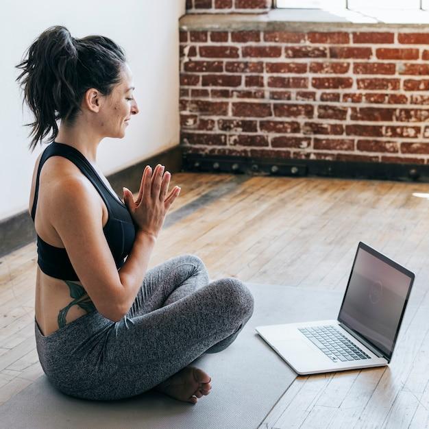 Donna sportiva in posa di anjali mudra con un laptop