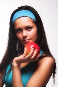 Donna sportiva che morde una mela rossa