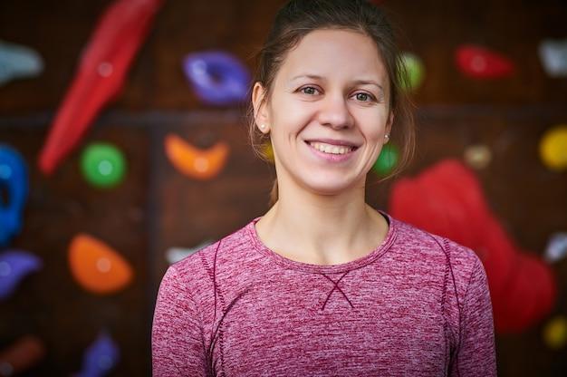 Donna sportiva nella sala di arrampicata su masso