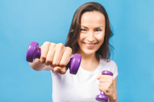 Donna sportiva facendo esercizi di boxe facendo colpo diretto con manubri