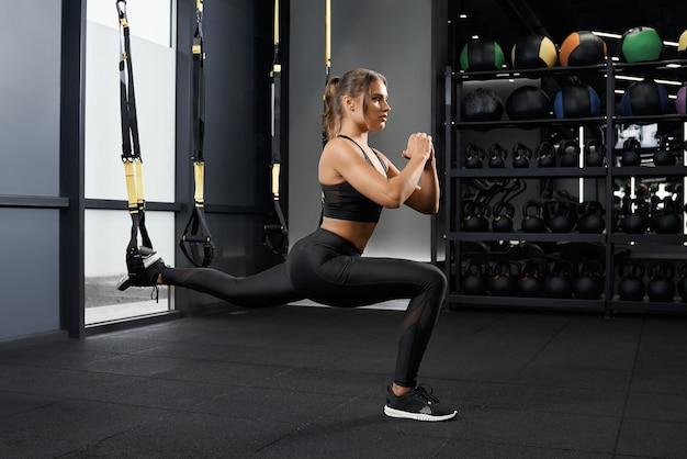 Donna sportiva che fa accovacciata con sistema trx
