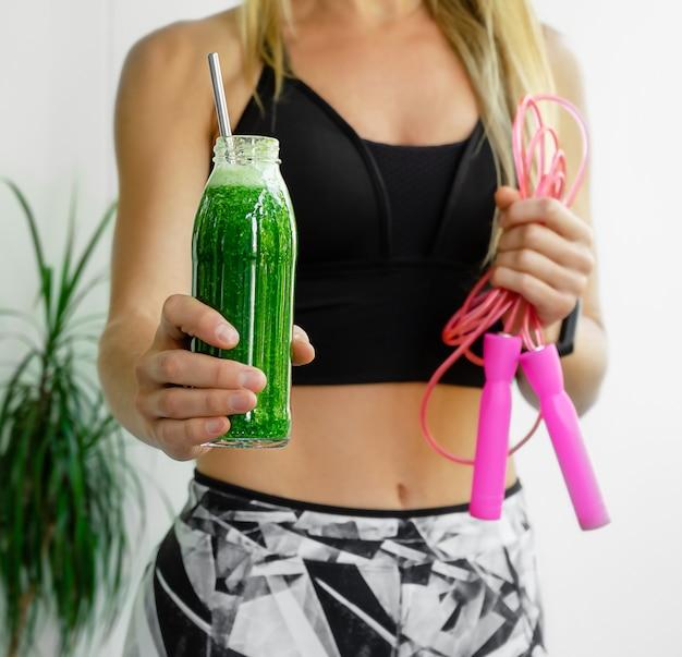 Donna sportiva che beve frullato alcalino vegano verde