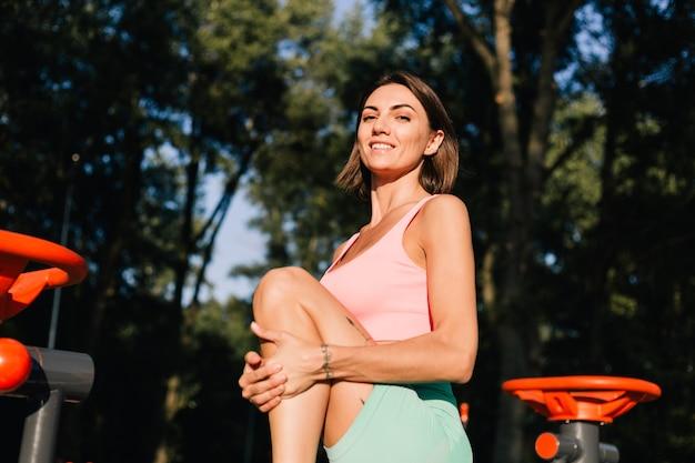 Donna sportiva che indossa abbigliamento sportivo al tramonto al campo sportivo allungando le gambe prima dopo l'allenamento