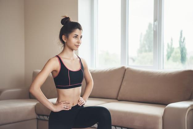 La donna sportiva a casa che indossa abbigliamento sportivo sta facendo fitness durante il blocco