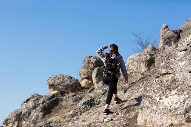 Donna sportiva sta scalando sulla cima della montagna scogliera con cielo blu