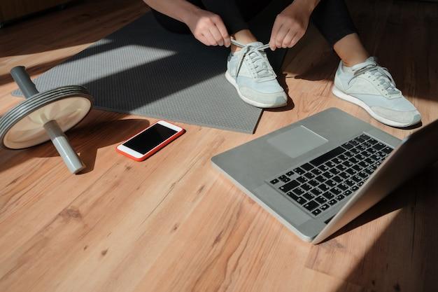Una donna sportiva è seduta sul pavimento e utilizza il laptop per l'allenamento online a casa in soggiorno