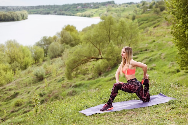 La donna sportiva sta allungando la gamba, esercitando sulla riva del fiume in estate.