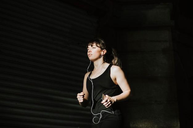 Donna sportiva che fa jogging in un vicolo buio