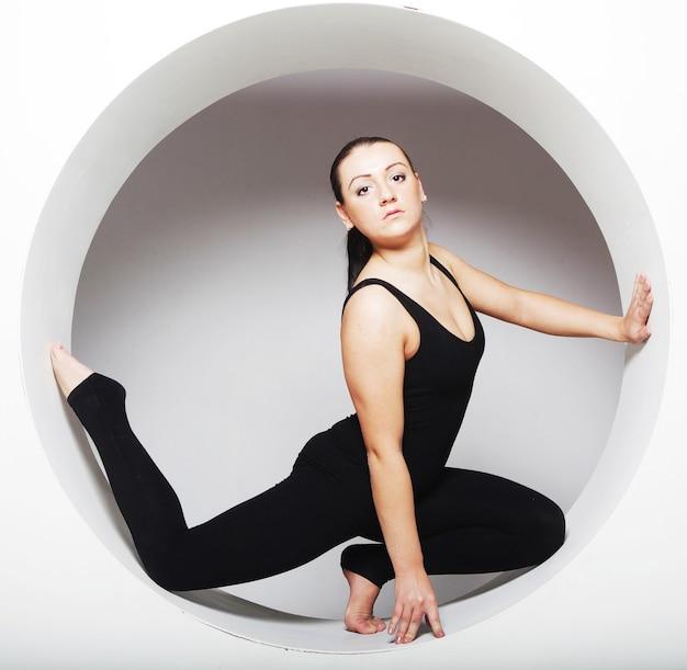 Donna sportiva che propone in un cerchio