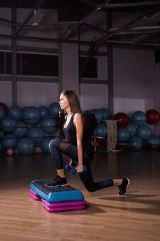 Donna sportiva pratica sulla piattaforma a gradini in palestra.