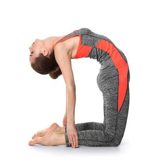 Yoga di pratica della donna sportiva su priorità bassa bianca