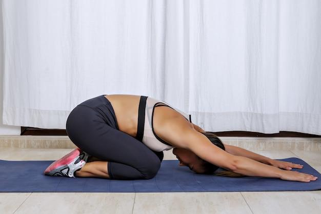 Donna sportiva che si rilassa nella posa del bambino