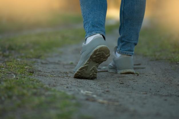 Corridore sportivo della donna in jeans e scarpe da ginnastica