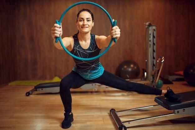 Donna sportiva in abbigliamento sportivo, allenamento pilates con anello sulla macchina ginnica in palestra. workuot fitness nel club sportivo.