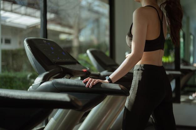 Una donna sportiva in piedi sul tapis roulant in palestra. concetto di fitness, sano, sport, stile di vita