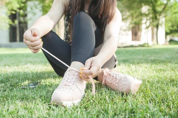 Donna sportiva che lega i lacci delle scarpe da corsa prima dell'allenamento all'aperto. prepararsi a correre